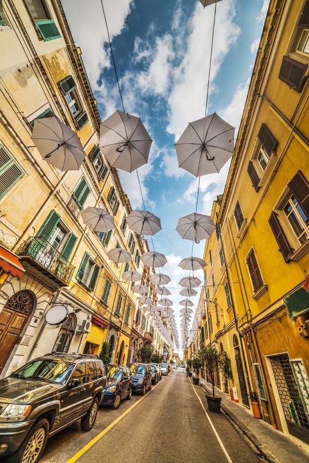 Άσπρες ομπρέλες σε μια στενή οδό στοκ φωτογραφίες