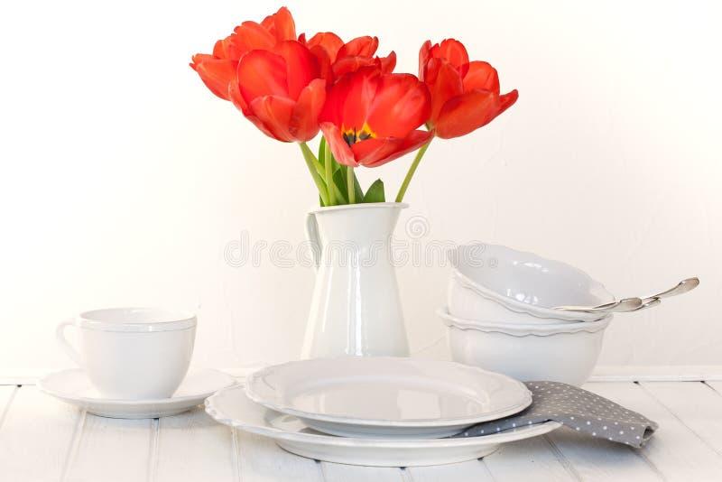 Άσπρες πιάτα, κύπελλα, και τουλίπες στοκ εικόνα