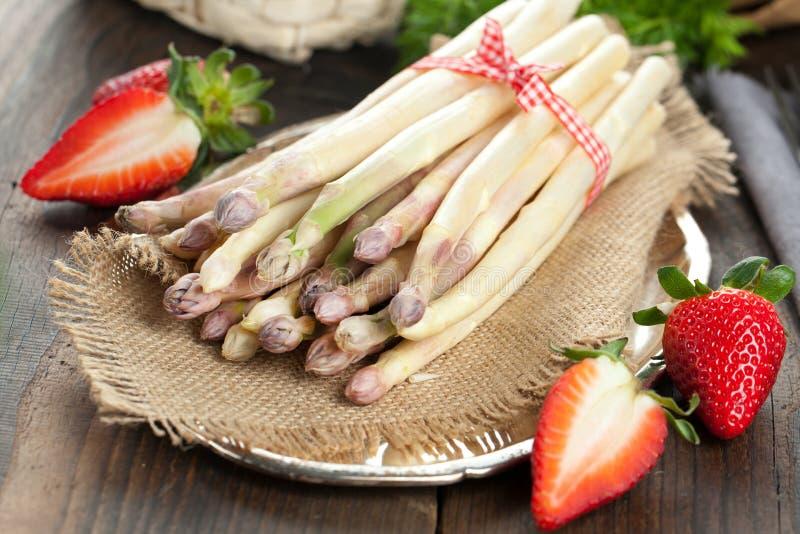 Άσπρες σπαράγγι και φράουλες στον ξύλινο πίνακα στοκ εικόνα με δικαίωμα ελεύθερης χρήσης