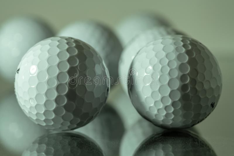 Άσπρες σφαίρες γκολφ που απεικονίζουν σε ένα πιάτο του γυαλιού στοκ φωτογραφία με δικαίωμα ελεύθερης χρήσης