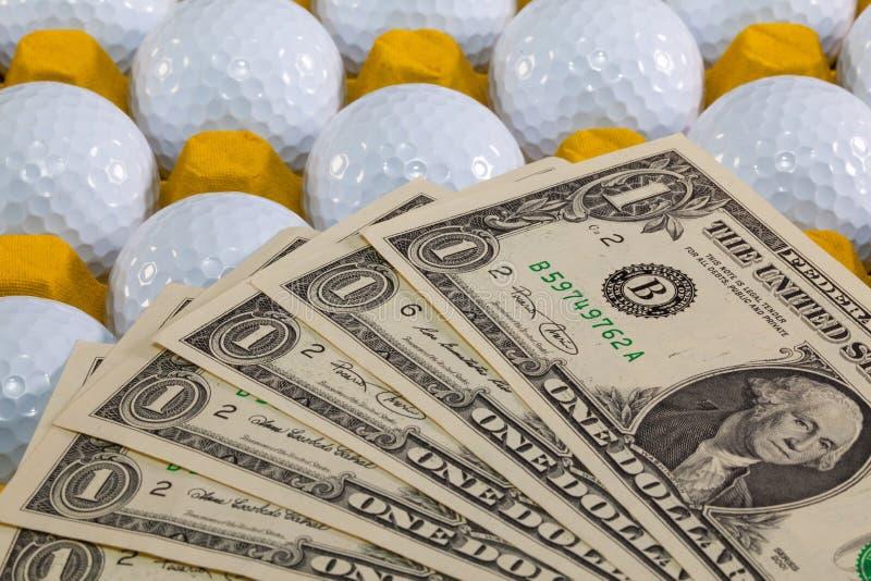 Άσπρες σφαίρες γκολφ στο κίτρινο κιβώτιο και τα αμερικανικά χρήματα στοκ φωτογραφίες