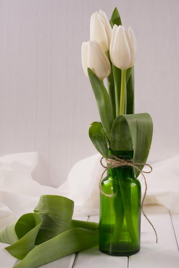Άσπρες τουλίπες στο πράσινο μπουκάλι γυαλιού στοκ εικόνες