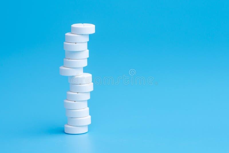 Άσπρες χάπια ή ταμπλέτες που συσσωρεύονται ο ένας στον άλλο στις διαφορετικές θέσεις στο μπλε υπόβαθρο στοκ φωτογραφίες με δικαίωμα ελεύθερης χρήσης