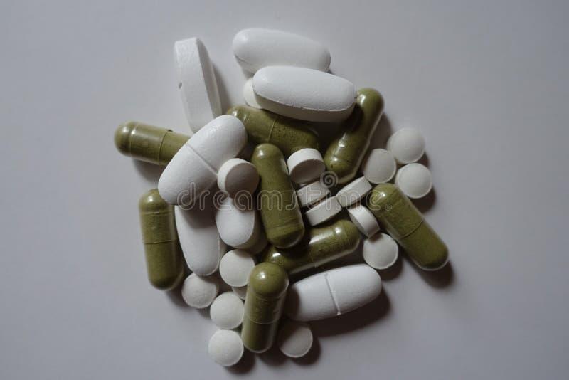 Άσπρες caplets ασβεστίου και ταμπλέτες βιταμίνη Κ, πράσινες moringa κάψες άνωθεν στοκ εικόνα