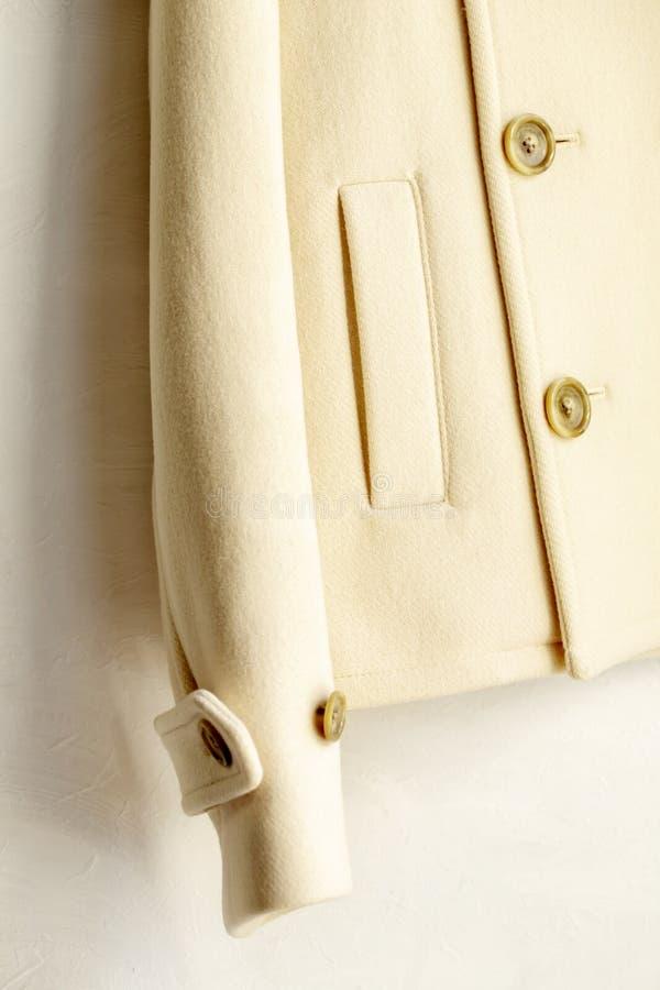 Άσπρη ένωση παλτών μαλλιού στην κρεμάστρα ενδυμάτων στο άσπρο υπόβαθρο στοκ εικόνες