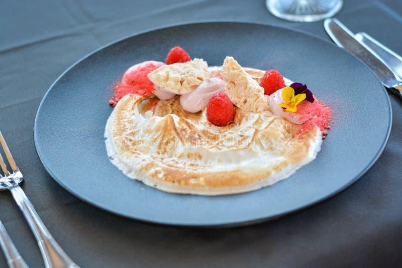 Άσπρη έρημος κρέμας με τα σμέουρα στο μαύρο πιάτο στο εστιατόριο στοκ φωτογραφίες