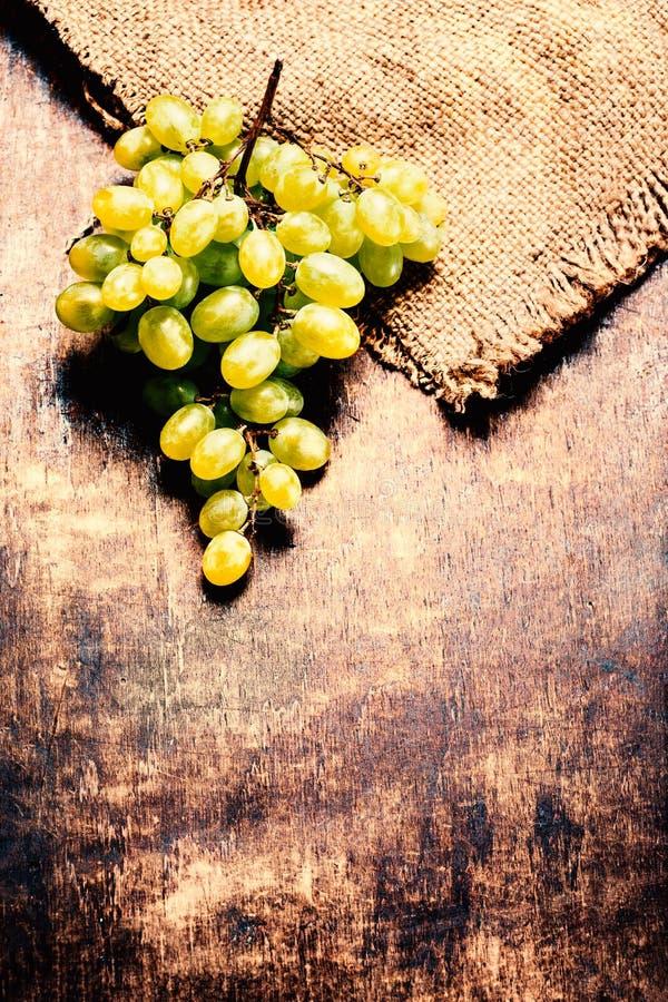 Άσπρη δέσμη σταφυλιών κρασιού πέρα από το ξύλινο υπόβαθρο Πράσινα σταφύλια macr στοκ εικόνα με δικαίωμα ελεύθερης χρήσης