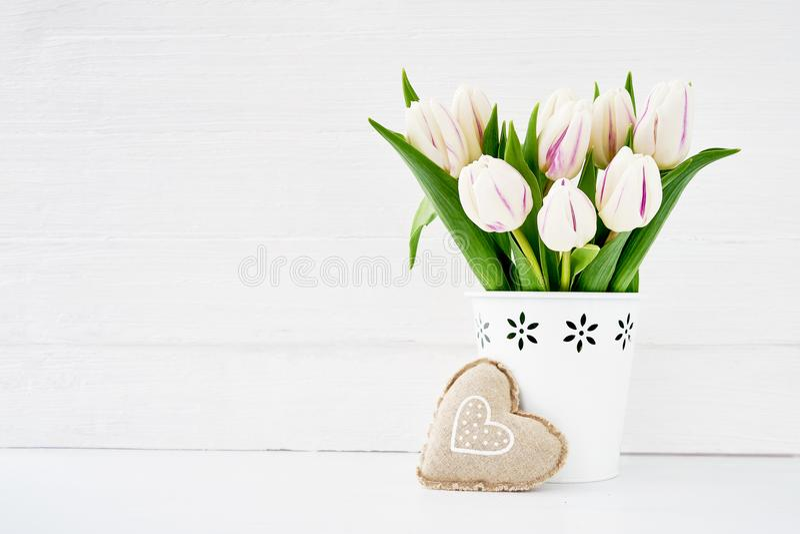 Άσπρη ανθοδέσμη τουλιπών στο άσπρο βάζο που διακοσμείται με την υφαντική καρδιά ανασκόπησης η μπλε κιβωτίων καρδιά δώρων ημέρας έ στοκ εικόνες με δικαίωμα ελεύθερης χρήσης