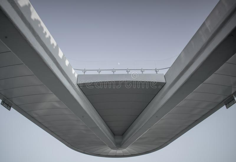 Άσπρη γέφυρα με το διαφανή φράκτη στο υπόβαθρο ουρανού και το μικρό μετά βίας αξιοπρόσεχτο φεγγάρι στοκ εικόνα