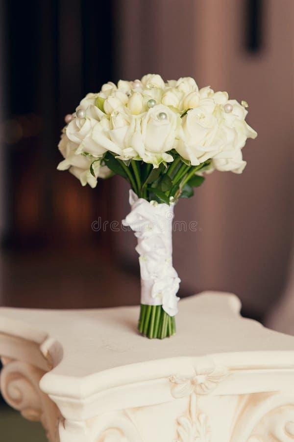 Άσπρη γαμήλια ανθοδέσμη τριαντάφυλλων σε έναν άσπρο πίνακα στοκ φωτογραφία με δικαίωμα ελεύθερης χρήσης