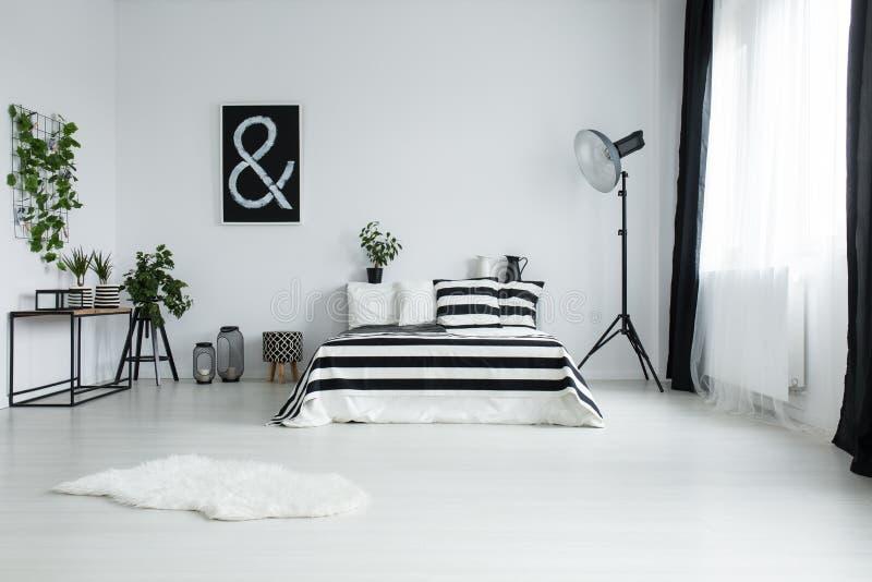 Άσπρη γούνα στο πάτωμα στη minimalistic κρεβατοκάμαρα στοκ εικόνα
