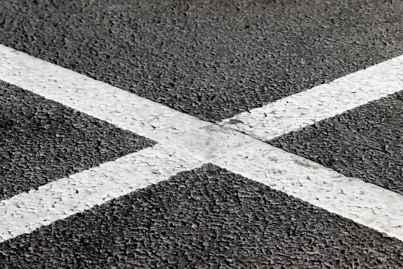 Άσπρη διαγώνια μορφή που χαρακτηρίζει στο δρόμο ασφάλτου στοκ εικόνες με δικαίωμα ελεύθερης χρήσης
