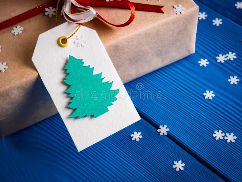Άσπρη ετικέτα με την εικόνα του έλατου Χριστουγέννων σε ένα δώρο με μια κόκκινη κορδέλλα στοκ εικόνες με δικαίωμα ελεύθερης χρήσης