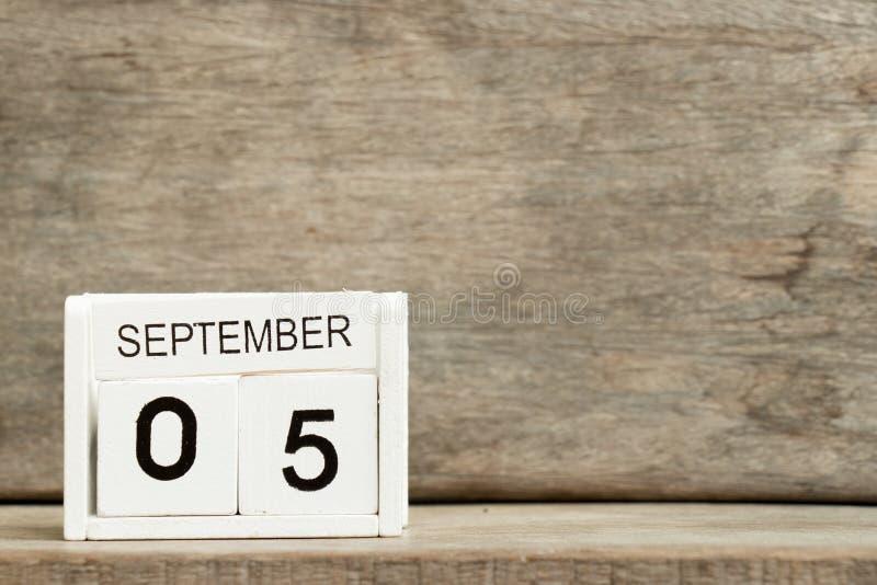 Άσπρη ημερολογιακή ημερομηνία 5 φραγμών και μήνας Σεπτέμβριος στο ξύλινο υπόβαθρο στοκ εικόνες