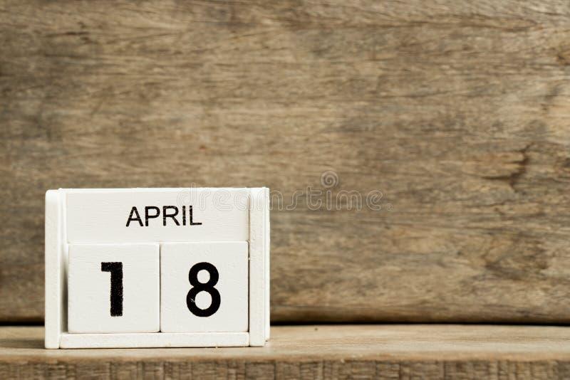 Άσπρη ημερολογιακή παρούσα ημερομηνία 18 φραγμών και μήνας Απρίλιος στο ξύλινο υπόβαθρο στοκ φωτογραφία