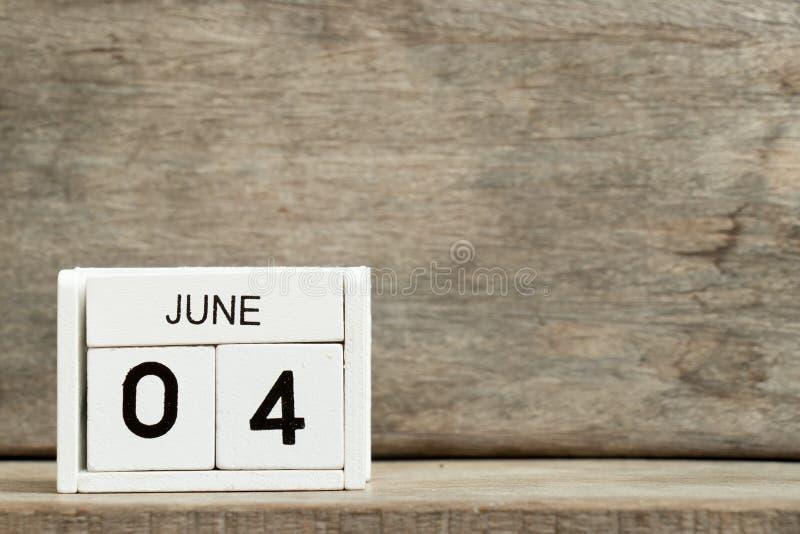 Άσπρη ημερολογιακή παρούσα ημερομηνία 4 φραγμών και μήνας Ιούνιος στο ξύλινο υπόβαθρο στοκ εικόνα