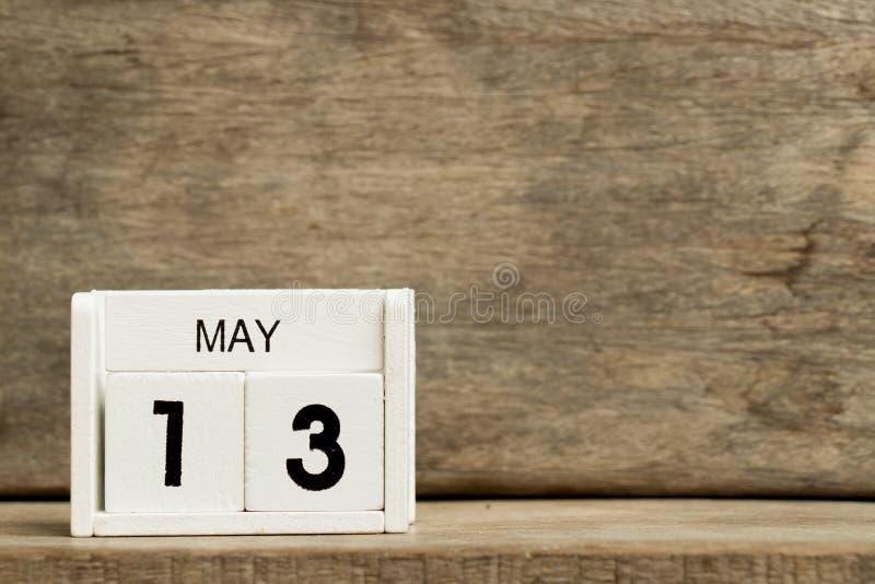 Άσπρη ημερολογιακή παρούσα ημερομηνία 13 φραγμών και μήνας Μάιος στο ξύλινο υπόβαθρο στοκ φωτογραφία