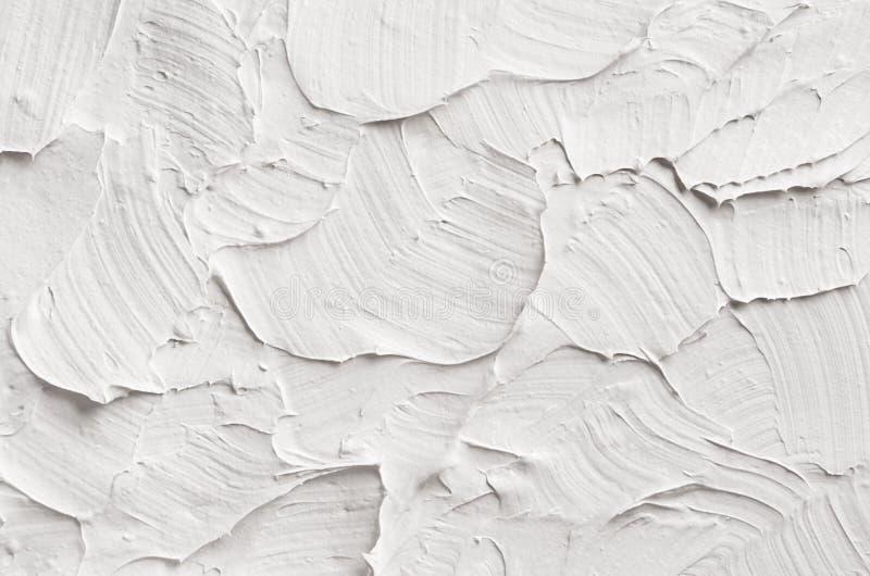 Άσπρη διακοσμητική αφηρημένη σύσταση ασβεστοκονιάματος με τις κατασκευασμένες κηλίδες στοκ φωτογραφία