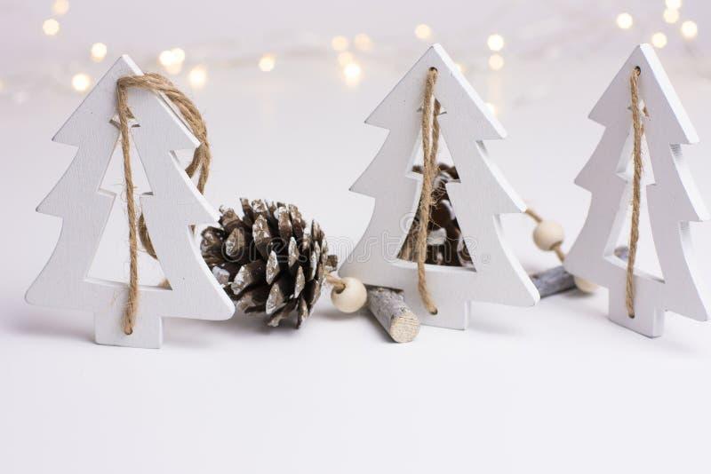 Άσπρη διακόσμηση Χριστουγέννων στο Σκανδιναβικό ύφος με τα ξύλινους treeas έλατου και τους κώνους πεύκων, bokeh φω'τα στο υπόβαθρ στοκ φωτογραφίες με δικαίωμα ελεύθερης χρήσης
