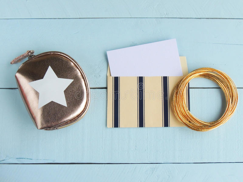 Άσπρη κάρτα, κρέμα και μπλε φάκελος, και χρυσά σακούλα και βραχιόλια στοκ εικόνες με δικαίωμα ελεύθερης χρήσης