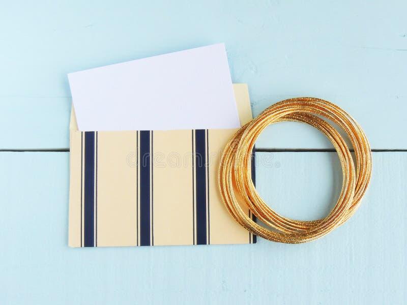 Άσπρη κάρτα, κρέμα και μπλε χρυσών βραχιόλια φακέλων και στοκ φωτογραφία
