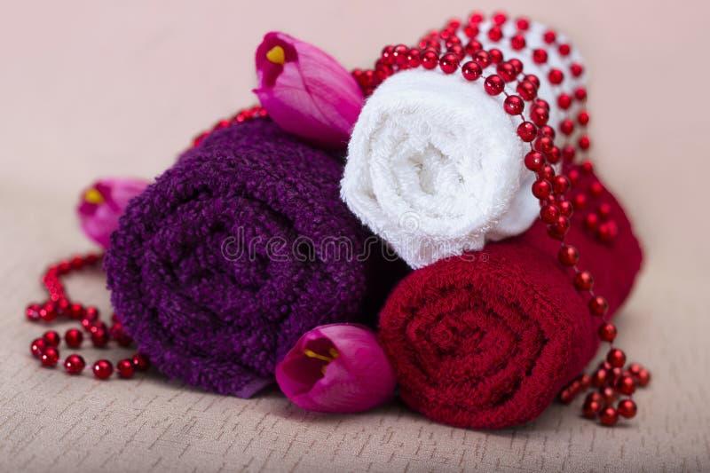 Άσπρη και κόκκινη πετσέτα γύρω από τις χάντρες και τα λουλούδια στοκ εικόνα