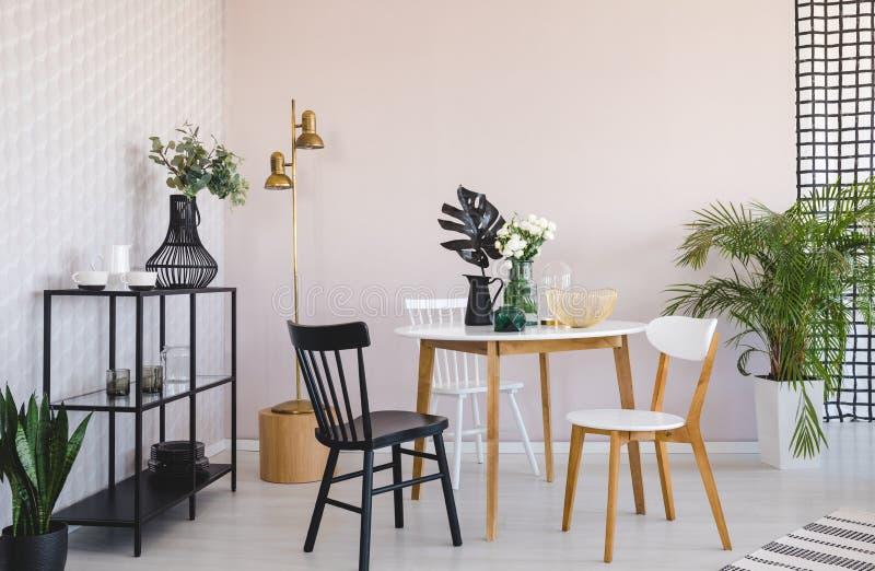 Άσπρη και μαύρη καρέκλα στον ξύλινο πίνακα με τις εγκαταστάσεις στο εσωτερικό τραπεζαρίας με το χρυσό λαμπτήρα Πραγματική φωτογρα απεικόνιση αποθεμάτων