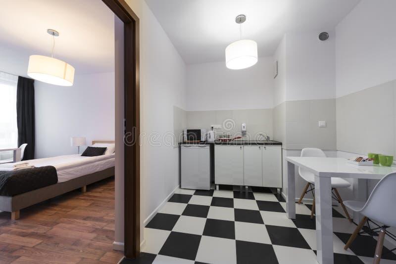 Άσπρη και μαύρη μικρή και συμπαγής κρεβατοκάμαρα τελών κουζινών στοκ εικόνες