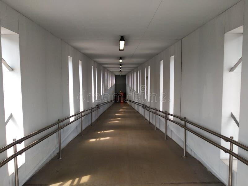 Άσπρη, καλά-ανάψοντη σήραγγα με τα κιγκλιδώματα ο δρόμος τείνει για να κατεβεί κάτω, κάτω από το έδαφος ή στο πάτωμα κατωτέρω ευκ στοκ φωτογραφίες