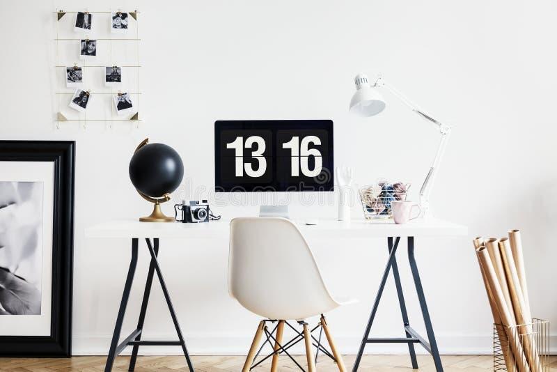 Άσπρη καρέκλα στον πίνακα με το λαμπτήρα και υπολογιστής γραφείου στο εσωτερικό χώρου εργασίας με την αφίσα Πραγματική φωτογραφία στοκ φωτογραφίες με δικαίωμα ελεύθερης χρήσης