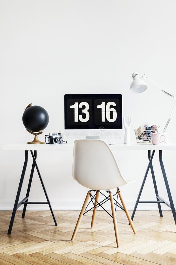 Άσπρη καρέκλα στο γραφείο με τον υπολογιστή γραφείου και σφαίρα στο εσωτερικό χώρου εργασίας με το λαμπτήρα Πραγματική φωτογραφία στοκ φωτογραφίες