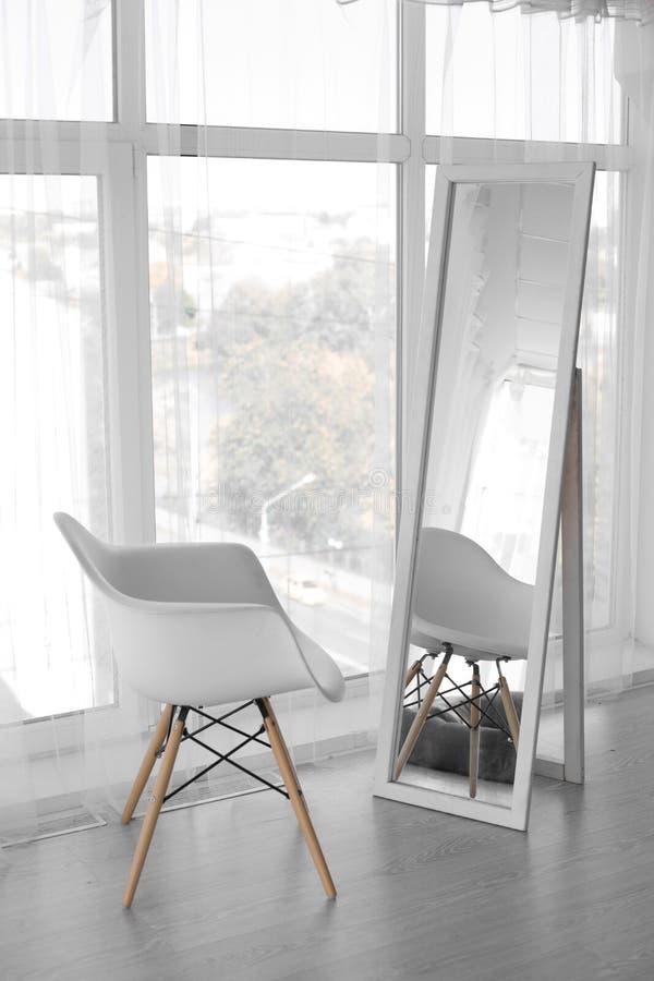 Άσπρη καρέκλα στο μεγάλο καθρέφτη Άσπρη έδρα στοκ εικόνες