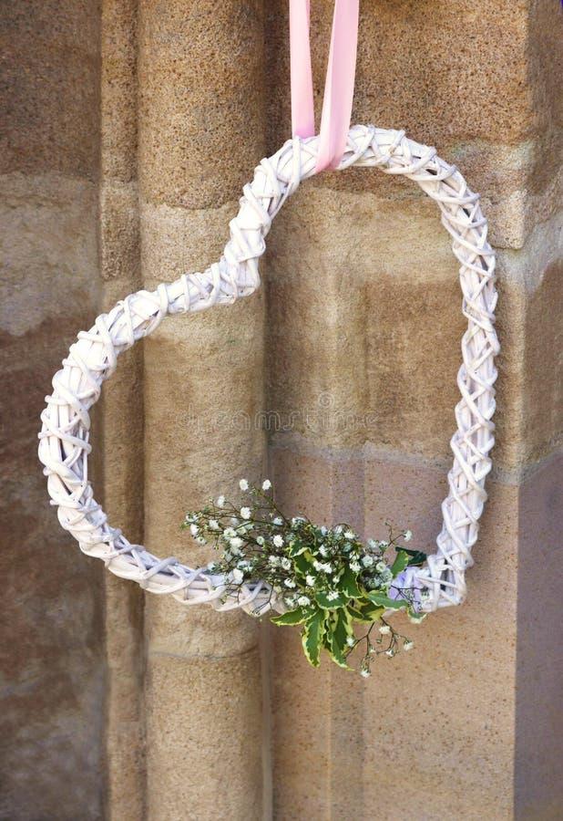Άσπρη καρδιά γαμήλιων συμβόλων με τα λουλούδια στοκ φωτογραφίες