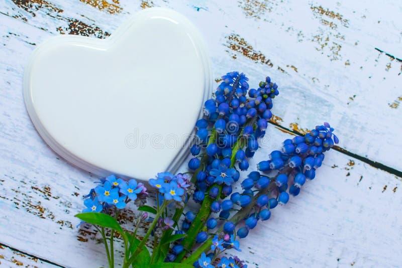 Άσπρη καρδιά πορσελάνης και μια ανθοδέσμη των μικρών μπλε λουλουδιών σε ένα ξύλινο ελαφρύ υπόβαθρο Γαμήλιο αυτοκίνητο στοκ φωτογραφία