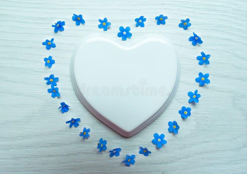 Άσπρη καρδιά πορσελάνης και μπλε λουλούδια που σχεδιάζονται με μορφή μιας καρδιάς σε ένα άσπρο υπόβαθρο r στοκ φωτογραφίες