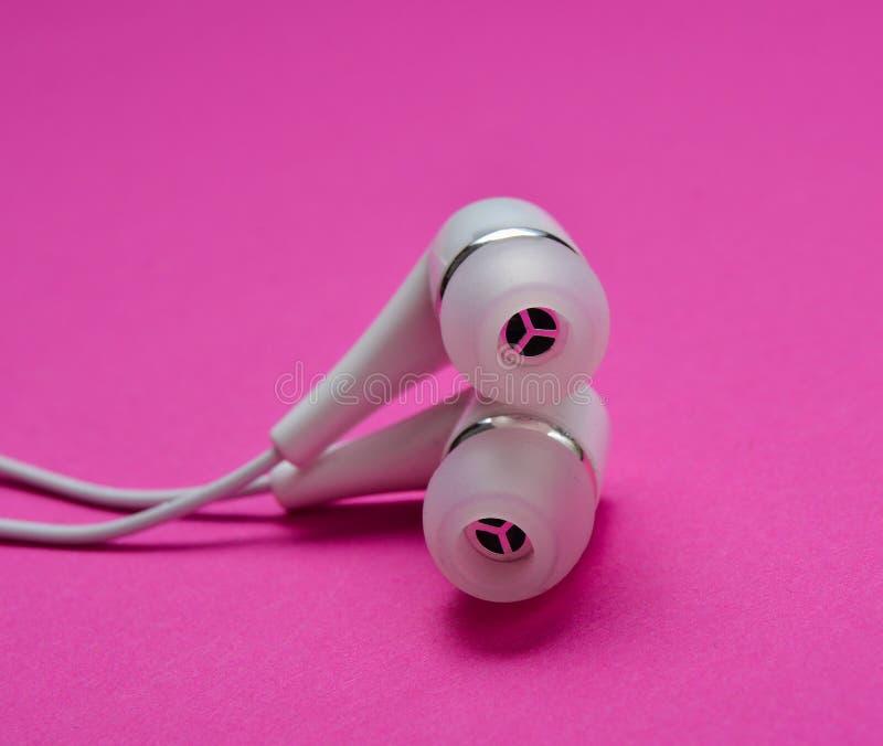 Άσπρη κενή κινηματογράφηση σε πρώτο πλάνο ακουστικών σε ένα ρόδινο υπόβαθρο στοκ φωτογραφίες