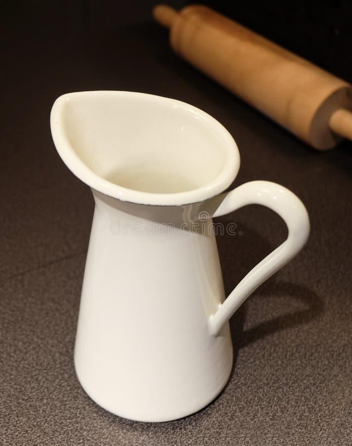 Άσπρη κεραμική κανάτα γάλακτος με την ξύλινη κυλώντας καρφίτσα στοκ εικόνες