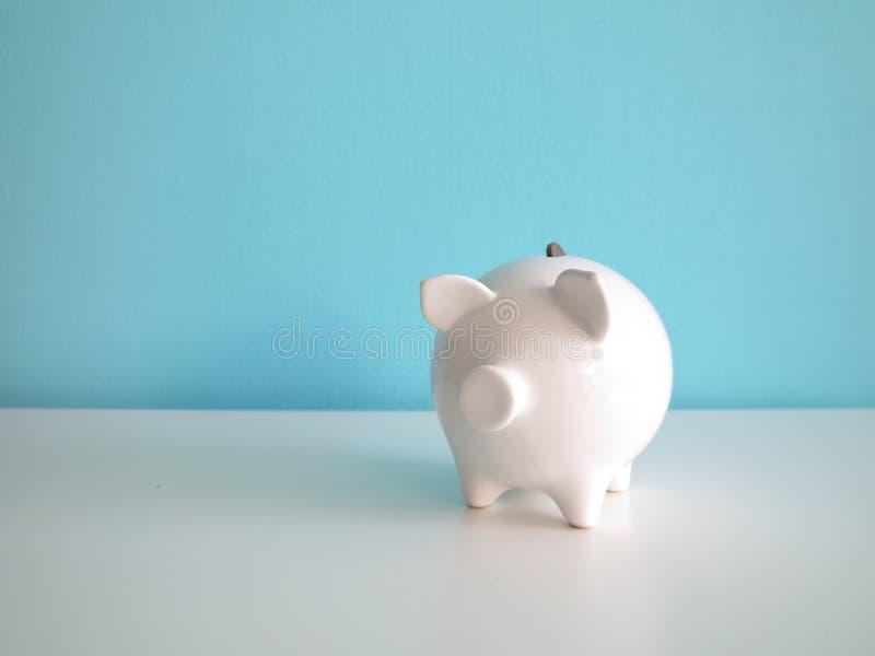 Άσπρη κεραμική piggy τράπεζα με τα ευρο- νομίσματα στον πίνακα στοκ φωτογραφία