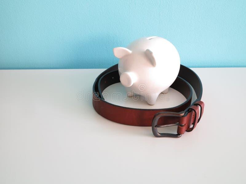 Άσπρη κεραμική piggy τράπεζα με την καφετιά ζώνη δέρματος γύρω στοκ φωτογραφίες με δικαίωμα ελεύθερης χρήσης