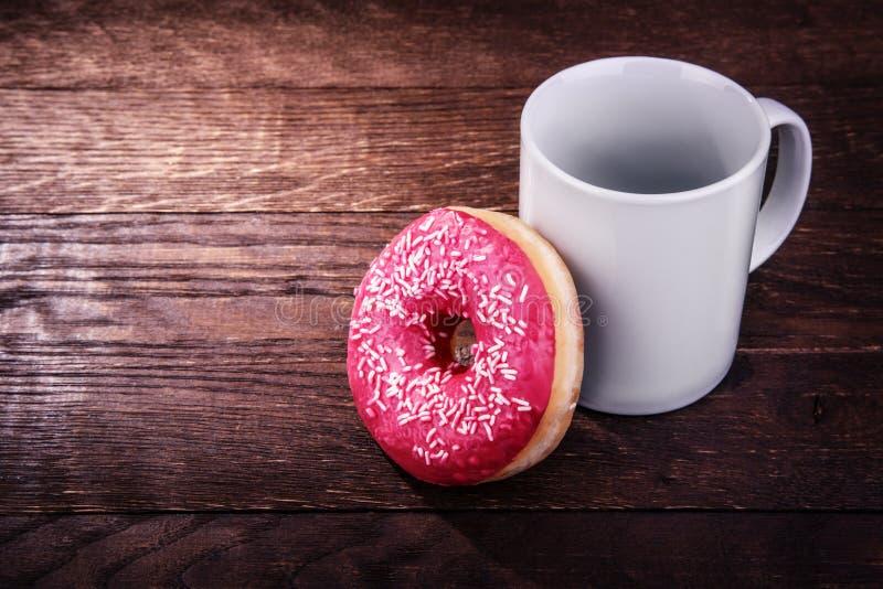Άσπρη κούπα και doughnut σε έναν ξύλινο στοκ εικόνες με δικαίωμα ελεύθερης χρήσης