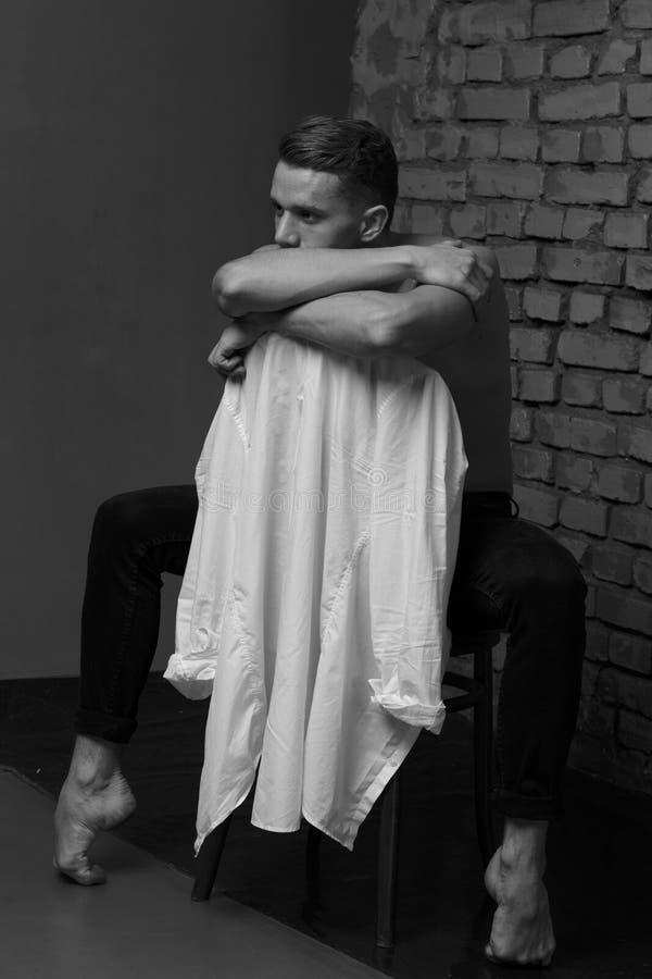 Άσπρη νέα συνεδρίαση τύπων σε μια καρέκλα κοντά σε έναν γκρίζο τουβλότοιχο, γραπτή φωτογραφία στοκ εικόνες με δικαίωμα ελεύθερης χρήσης