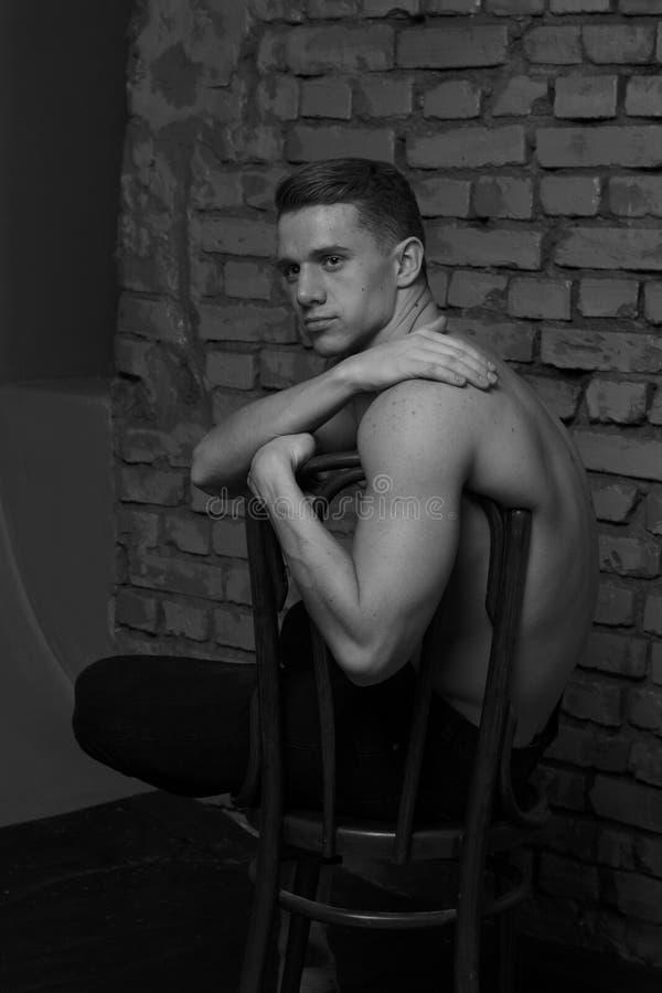 Άσπρη νέα συνεδρίαση τύπων σε μια καρέκλα κοντά σε έναν γκρίζο τουβλότοιχο, γραπτή φωτογραφία στοκ φωτογραφία