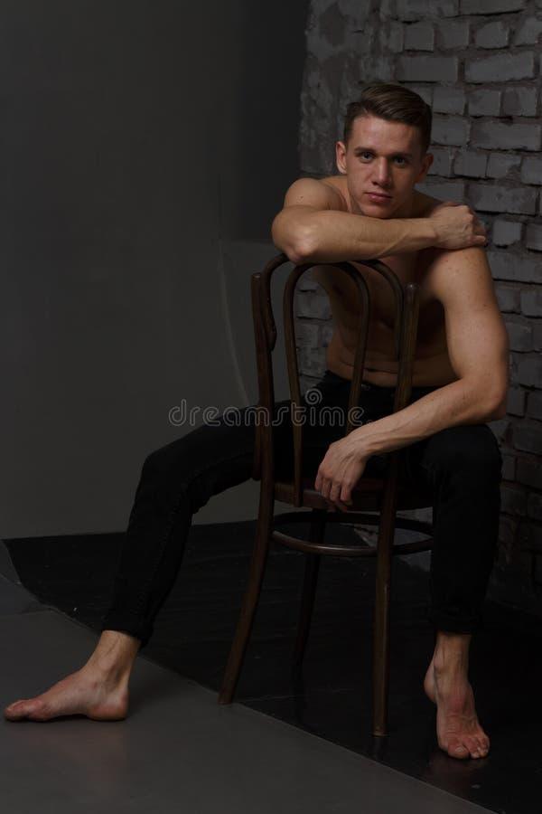 Άσπρη νέα συνεδρίαση τύπων σε μια καρέκλα κοντά σε έναν γκρίζο τουβλότοιχο, γραπτή φωτογραφία στοκ φωτογραφία με δικαίωμα ελεύθερης χρήσης