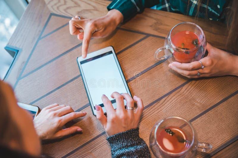 Άσπρη οθόνη του lap-top γυναίκα στην ομιλία καφέδων πίνοντας τσάι φρούτων στοκ εικόνα με δικαίωμα ελεύθερης χρήσης