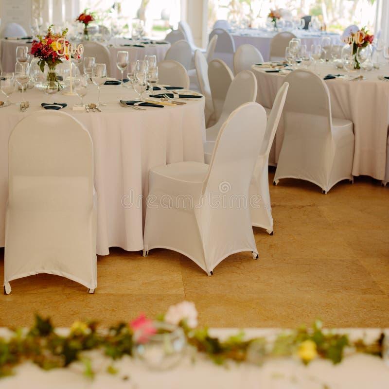 Άσπρη οργάνωση γευμάτων για έναν γάμο Πίνακες και έδρες Τετραγωνική εικόνα στοκ εικόνες