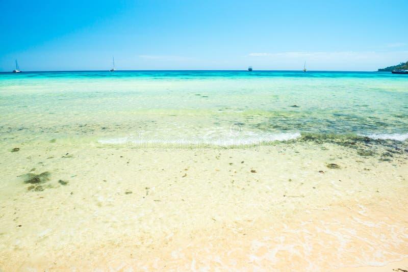 Άσπρη παραλία άμμου και σαφές θαλάσσιο νερό κάτω από το μπλε ουρανό στοκ εικόνες