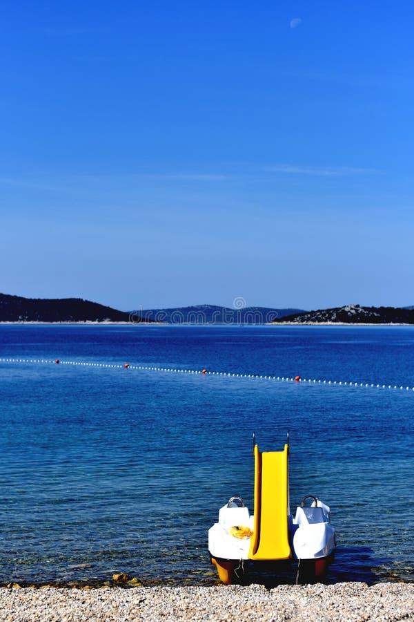 Άσπρη παραλία με την κίτρινη βάρκα pedalo, κάθετο μπλε τοπίο στοκ φωτογραφία
