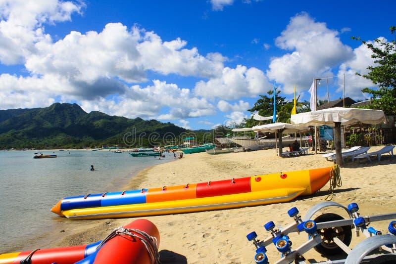 Άσπρη παραλία άμμου ενάντια σε έναν σαφή μπλε ουρανό, τη θέα βουνού και μια βάρκα μπανανών δραστηριότητας νερού στοκ φωτογραφία