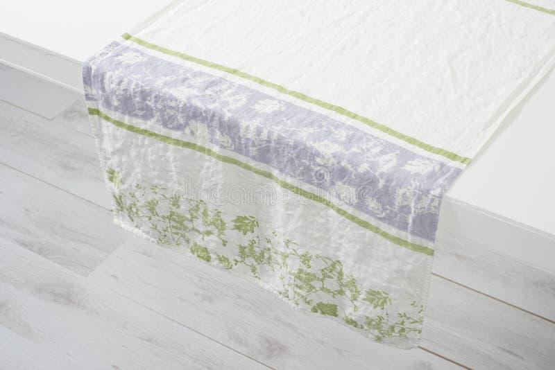 Άσπρη πετσέτα χεριών με τις πράσινες Floral εμφάσεις πέρα από τον άσπρο μετρητή στοκ εικόνες