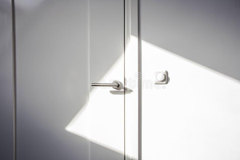 Άσπρη πόρτα κινηματογραφήσεων σε πρώτο πλάνο με το φως του ήλιου Η πόρτα χρωμίου, το φως ανάβει το σύγχρονο σχέδιο τοίχων κενό κα στοκ εικόνα